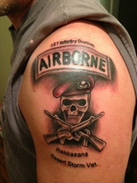 Coloured symbol of us army tattoo on shoulder